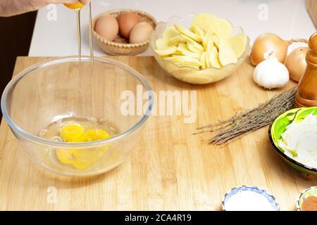 craquer les œufs dans la cuisine pour préparer une omelette Banque D'Images