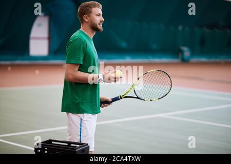 Jeune homme barbu en vert sportwear joue au tennis sur un court intérieur, tenant la balle dans la main. Banque D'Images