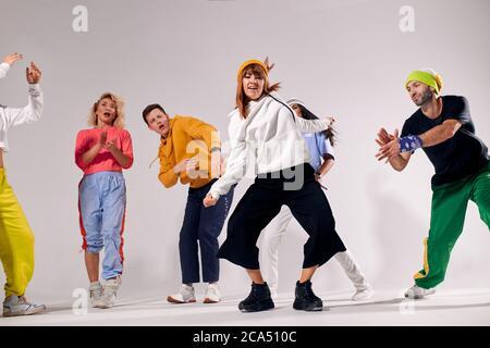 Jeune danseuse en mouvement, vêtue de sweat à capuche blanc et de pantalon noir large, montrant la danse expressive, regardant la caméra avec l'expression gaie, env Banque D'Images