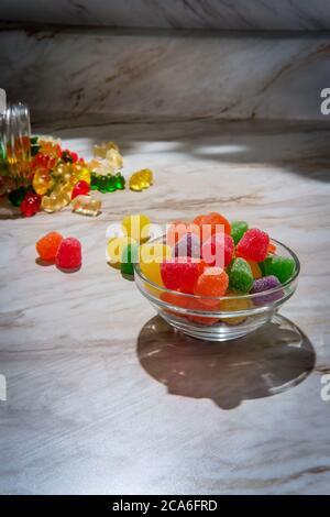 Bonbons enrobés de sucre granulé avec un pot déversé d'ours délicieux en arrière-plan