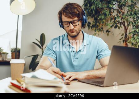 Un jeune homme en chemise bleue est assis à la table et étudie avec un ordinateur portable Banque D'Images