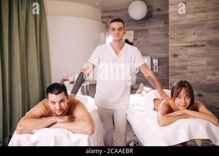 beau masseur talentueux debout entre une femme et un homme allongé sur les tables de massage. les gens sont prêts pour le massage Banque D'Images