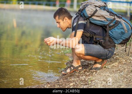 un bon gars qui a l'air de se laver le visage sur la rivière. le voyageur assoiffé boit de l'eau de la rivière. photo vue de côté en gros plan Banque D'Images