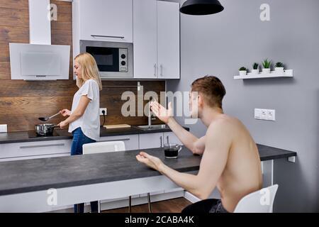 un homme mécontent indigné s'indignant de sa femme dans la cuisine, un couple malheureux et marié arguent chaque jour, ils ont une crise dans la famille. l'homme en colère n'a pas assez