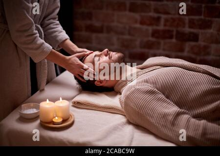 Salon de beauté, concept de traitement. Jeune homme caucasien obtenir un massage sur la tête et le visage allongé sur le bureau avec les yeux fermés, calme