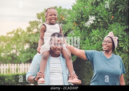 Les familles afro-américaines heureuses qui marchaient à l'extérieur ont passé un excellent moment ensemble dans le jardin à la maison