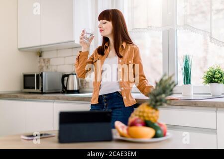 Jeune femme souriante en tenue décontractée, buvant de l'eau minarl, tout en se tenant dans la cuisine moderne à la maison, en commençant sa journée active. Prêt à manger