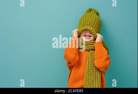 Portrait d'hiver d'un enfant heureux portant un bonnet, un snood et un chandail tricotés. Fille s'amusant, jouant et riant sur fond sarcelle. Mode.