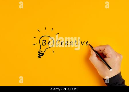 La main masculine écrit les mots être créatif et dessine une ampoule sur fond jaune. Créativité et innovation.