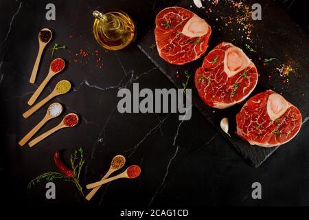 Os de tige de bœuf cru et épices pour préparer le plat d'ossobuco sur fond noir. Vue de dessus.