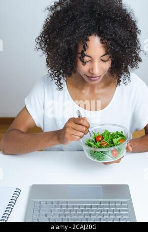 belle jeune femme noire mangeant une salade devant un ordinateur portable moderne avec fond blanc