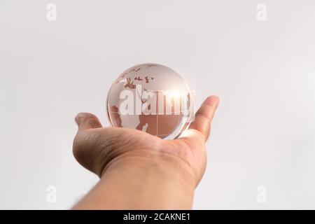 Main homme tenant la terre de verre sur fond isolé. Notion de protection de l'environnement et de faiblesse fragile du monde