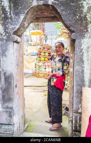 Bali / Indonésie - 15 août 2018 : Portrait d'une femme bouddhiste souriant à la porte d'un petit temple local tenant des fruits comme offrande religieuse