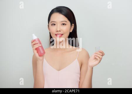 Belle femme pulvérisant sur le visage isolé sur fond blanc