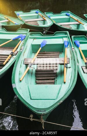 Vieux bateaux verts vides avec des verrats en bois sur le lac de proximité. Bateaux de plaisance de la vieille rangée. Location de bateaux Banque D'Images