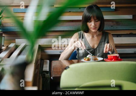 Femme qui aime manger du gâteau dans un café. Tir frontal à travers une plante.