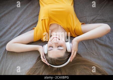 Jeune femme souriante dans un casque à écouter de la musique ou un livre audio sur son lit, vue de dessus Banque D'Images