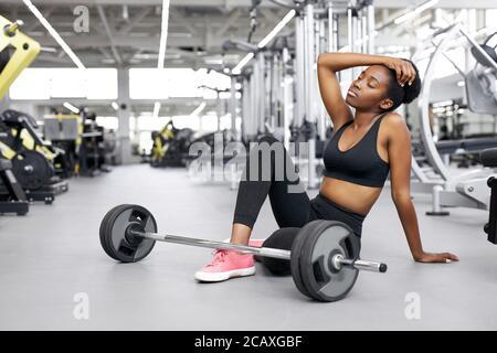 black afro fit femme fatiguée après des exercices haltérophilie, jeune femme assis à côté de barbell, épuisé