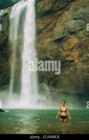 Femme avec une chute d'eau dans le dos ayant le plaisir.