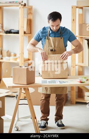 Portrait complet d'un homme mature portant des commandes d'emballage de tablier tout en étant debout près d'une table en bois, employé du service de livraison de nourriture Banque D'Images