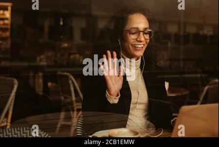 Femme d'affaires ayant un appel vidéo sur son ordinateur portable. Femme professionnelle assise dans un café avec des écouteurs et se portant sur un ordinateur portable. Banque D'Images