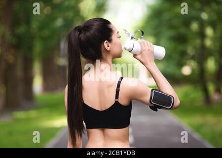 Vue arrière de la femme de fitness asiatique qui boit de l'eau après le jogging dans le parc