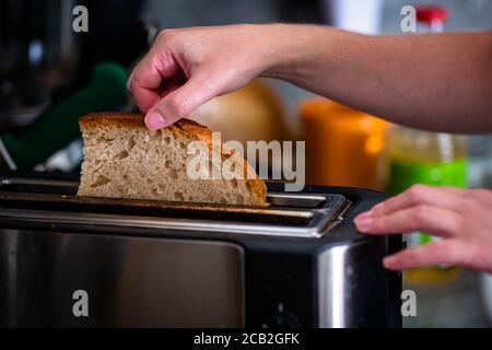 Mains fille tire dans pain de tranche traditionnel. Femme à la main mettant du pain de blé entier frais dans le grille-pain à la cuisine. Flou d'arrière-plan des objets de cuisine. Banque D'Images