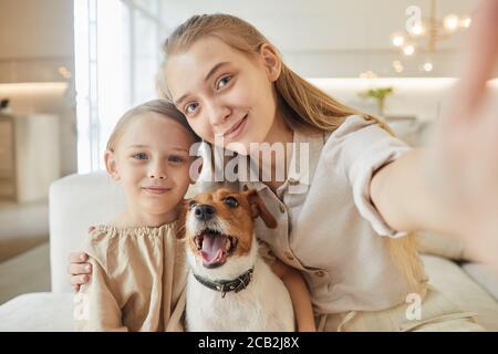 Portrait aux tons chauds de deux sœurs qui prennent le selfie avec leur chien et regardent l'appareil photo tout en étant assis sur un canapé dans un espace minimal à l'intérieur de la maison Banque D'Images