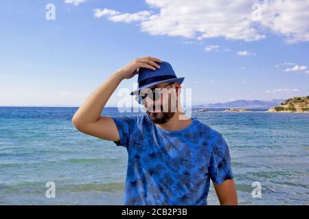 jeune homme en chapeau bleu sur la plage