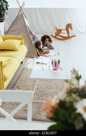 vue en grand angle de la baby-sitter et du dessin d'enfant en position allongée dans le wigwam jouet Banque D'Images