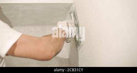 Ouvrier de construction plâtrage un mur avec une spatule dans un concept de rénovation