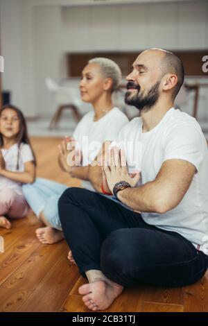 Belle famille méditant à la maison, assis sur le sol. Famille, sport, yoga concept. Couleurs blanches