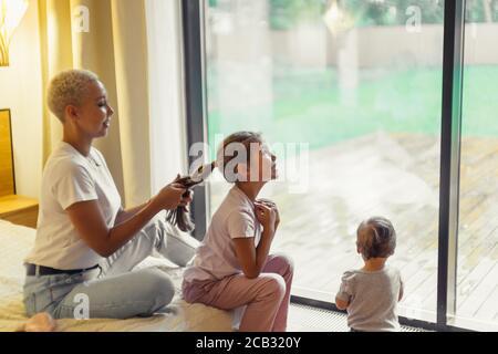 La jeune femme a bradé les cheveux à sa fille, assise au lit le week-end. Fenêtre panoramique d'arrière-plan, pied de bébé en face de la fenêtre Banque D'Images