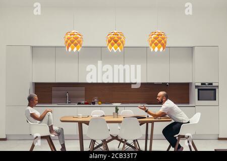 Un couple familial s'assoit l'un en face de l'autre à la maison sur la table et parle de leurs relations. L'homme parle fort, des gestes. Concept de relation de personnes Banque D'Images