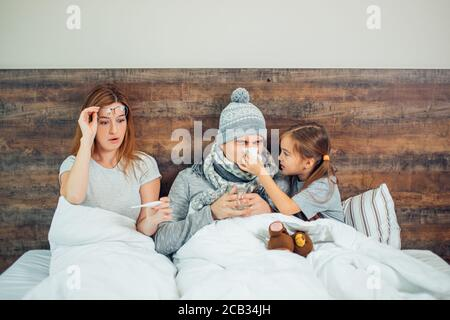 famille caucasienne malade, couchée au lit ensemble, souffrant de maladie. Un homme, une femme et une fille malsains se traitant à la maison