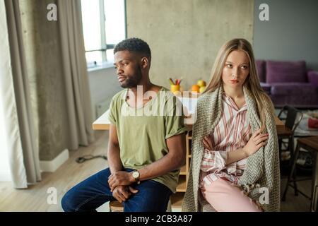 Jeune couple interracial malheureux ayant des problèmes dans la relation, assis dans la salle de séjour à la maison