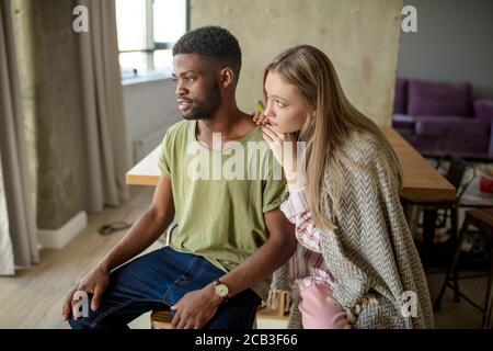 La femme blonde caucasienne consoles et soutient son ami hippster africain, qui a le regard sombre et frustré, le couple est assis dans la vie confortable