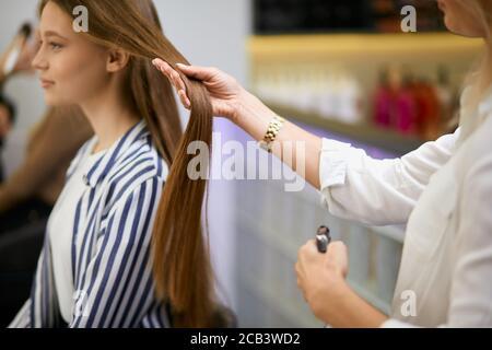 coiffeur caucasien prudent tenant les cheveux du client dans les mains, va couper les bouts de cheveux, faisant la coiffure à la jeune fille client assis sur la chaise oppos