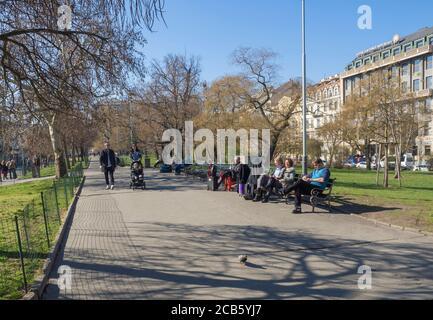 Prague, République tchèque, 23 mars 2019: Personnes marchant et assis sur un banc sur la route du parc, en face de la gare principale de Prague appelée Hlavni nadrazi Banque D'Images