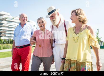 Groupe d'aînés marchant et s'amusant dans la ville Banque D'Images