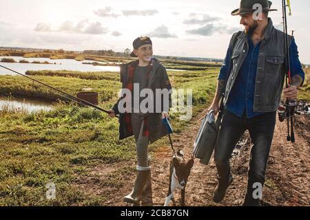 Joyeux sourire père et fils vont pêcher ensemble. Ils marchent le long du lac par temps ensoleillé. Ils marchent le long du sentier familial par temps ensoleillé. Banque D'Images