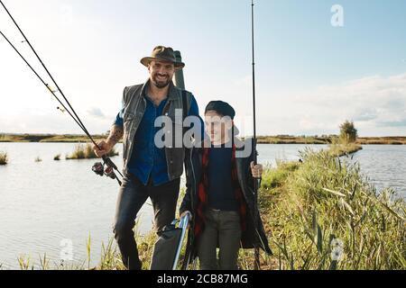 Le père et le fils vont sur l'île dans le lac, cherchez un lieu de pêche familiale. Ils portent des cannes à pêche. Journée chaude et ensoleillée. Banque D'Images
