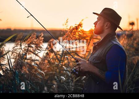 Homme barbu caucasien dans la pêche au chapeau en roseau près du lac. Coucher de soleil. Banque D'Images