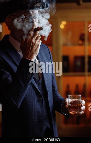 Concept de la vieillesse, de la richesse, de la prospérité et de l'expérience. Prosperious confiant de l'homme à barbe grise et à lunettes, porter grand dandy hat fumeurs ci