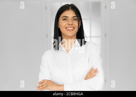 Portrait de charmant comptable, beau avocat en chemise blanche debout avec des bras croisés dans le poste de travail, souriant et regardant la caméra Banque D'Images