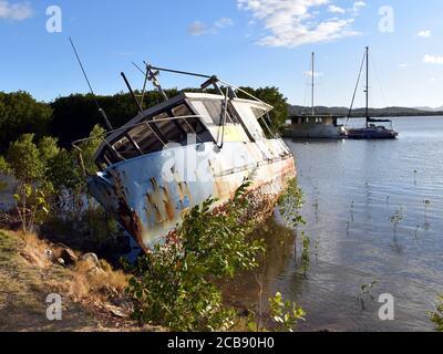 Un bateau négligé sur son côté dans les mangroves de loin Nord du Queensland Banque D'Images