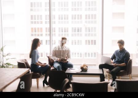 Trois hommes d'affaires et des femmes collègues dans le cadre du travail de formalwear à l'aide d'un ordinateur portable