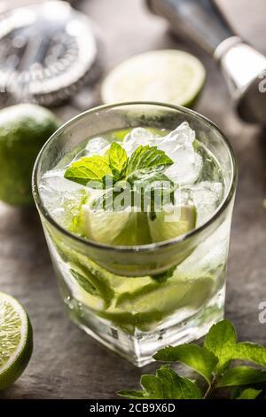 Boisson cocktail Mojito avec rhum blanc citron vert fines herbes et soda sur le comptoir du bar
