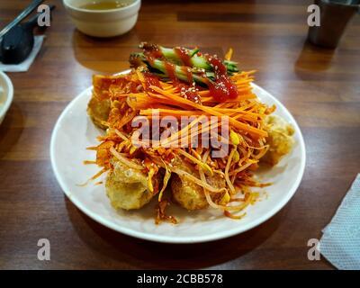 Bibim Mandu ou Bibim Mandoo. Boulettes mixtes de style coréen. Potstickers poêlés mélangés à de la salade et une sauce sucrée, acidulée et épicée addictive.