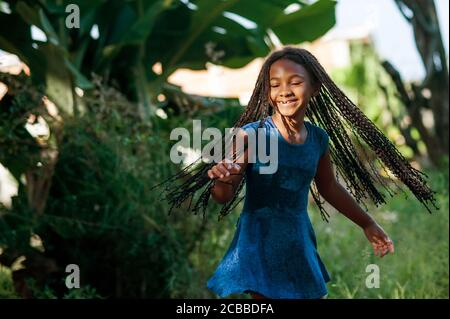 Jeune fille africaine jouant et dansant dans la nature Banque D'Images